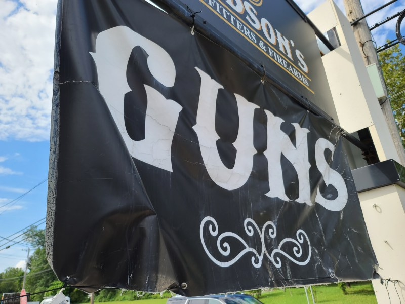 A sign advertising guns outside a store