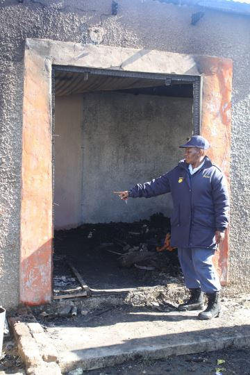 GUTTED: Police spokesman Captain Namhla Mdleleni at the house where three children burnt to death in Mlungisi on Saturday morning Picture: BHONGO JACOB