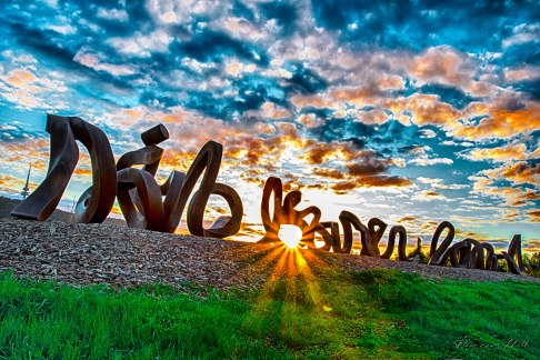 Sculpture of words wide brown land on a scene with the sun rising through the b in the word brown.