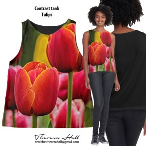 A sleevless top with tulips on the front. The tone of the tulips is in orangy, pinky, reddy colours with a yellow tulip in the background. The back of the garment is black.