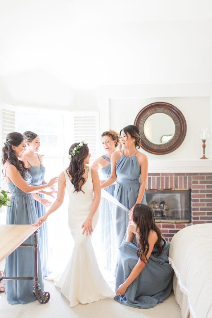 Bridesmaids helping a bride get ready on wedding day Colorado Wedding Photographer