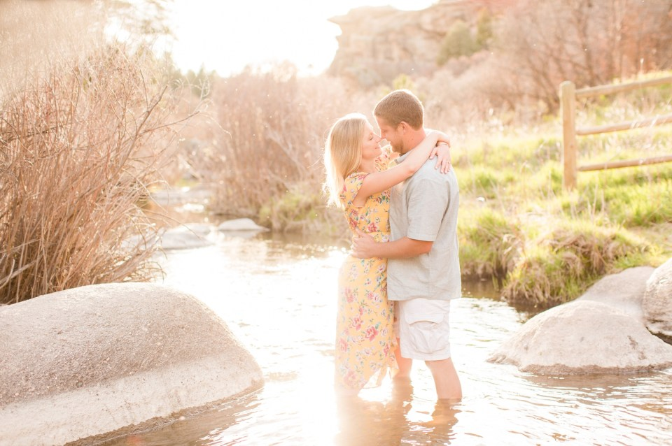 Couple standing in a stream at Castlewood State Park in Colorado. Engagement Session in Castlewood State Park.