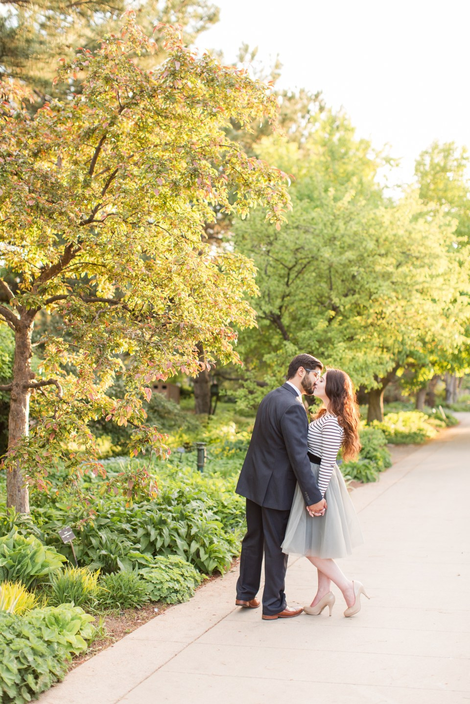 Girl in a grey tule skirt and stripped top for an engagement session at the Denver Botanic garden. Couple kissing on a pathway at the Denver Botanic Gardens