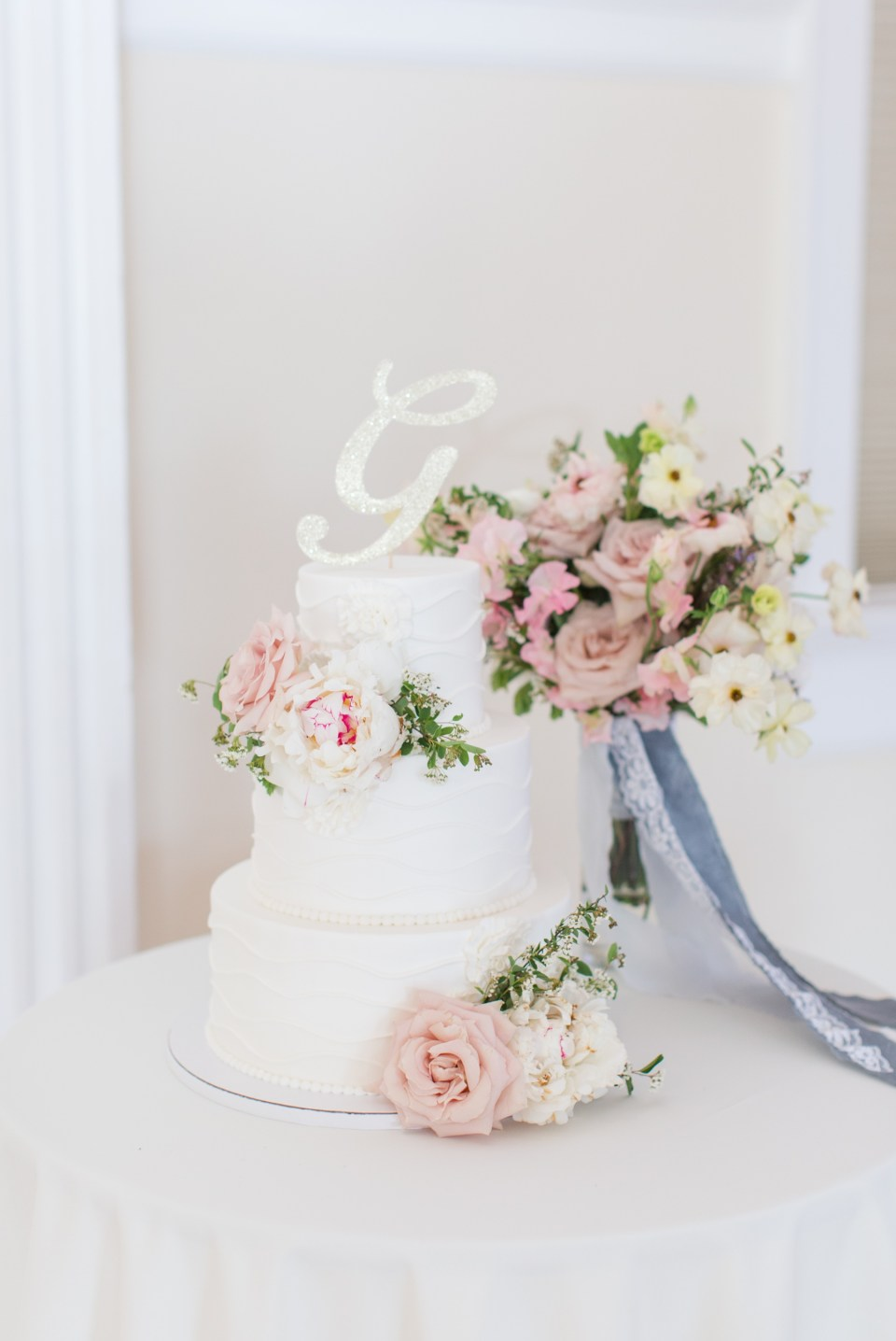 Classic white wedding cake with peonies. Colorado wedding photographer.