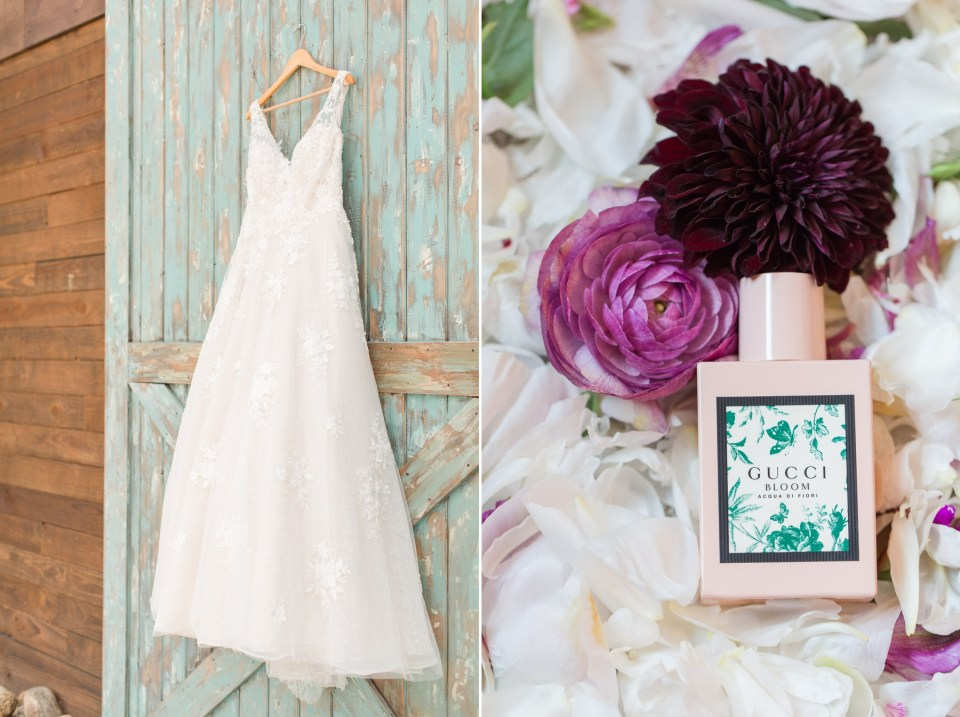 Gucci bloom wedding perfume sitting ontop of flower pettlers. A lace wedding dress hung up on a barn door.