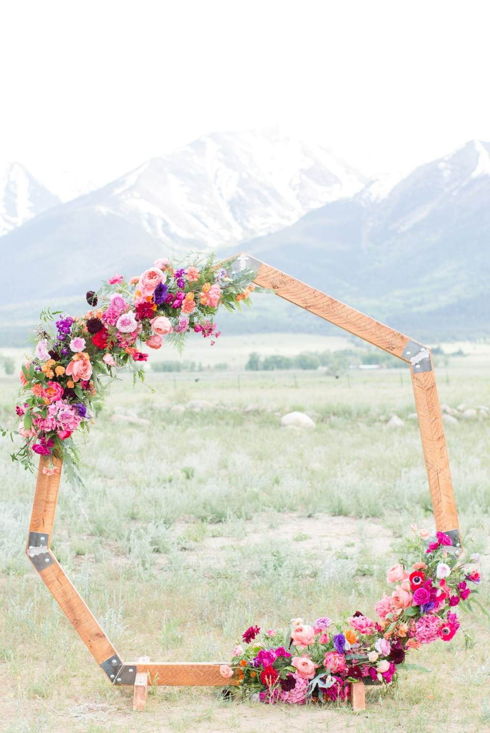 Hexagon Ceremony arch set up at the base of a mountain in Colorado. Colorful wedding flowers by lace and lilies.