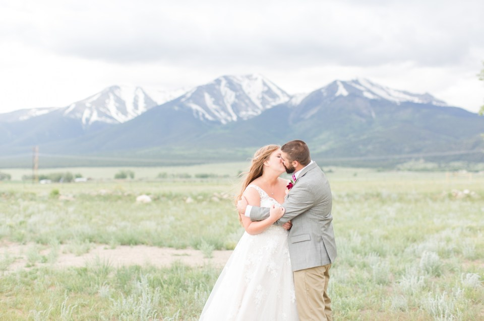 Bride and groom kissing during portraits at the base of a mountain in Colorado. Theresa Bridget Photography, Colorado Wedding Photographer. The barn at sunset ranch wedding venue with mountain views in Buena Vista Colorado.