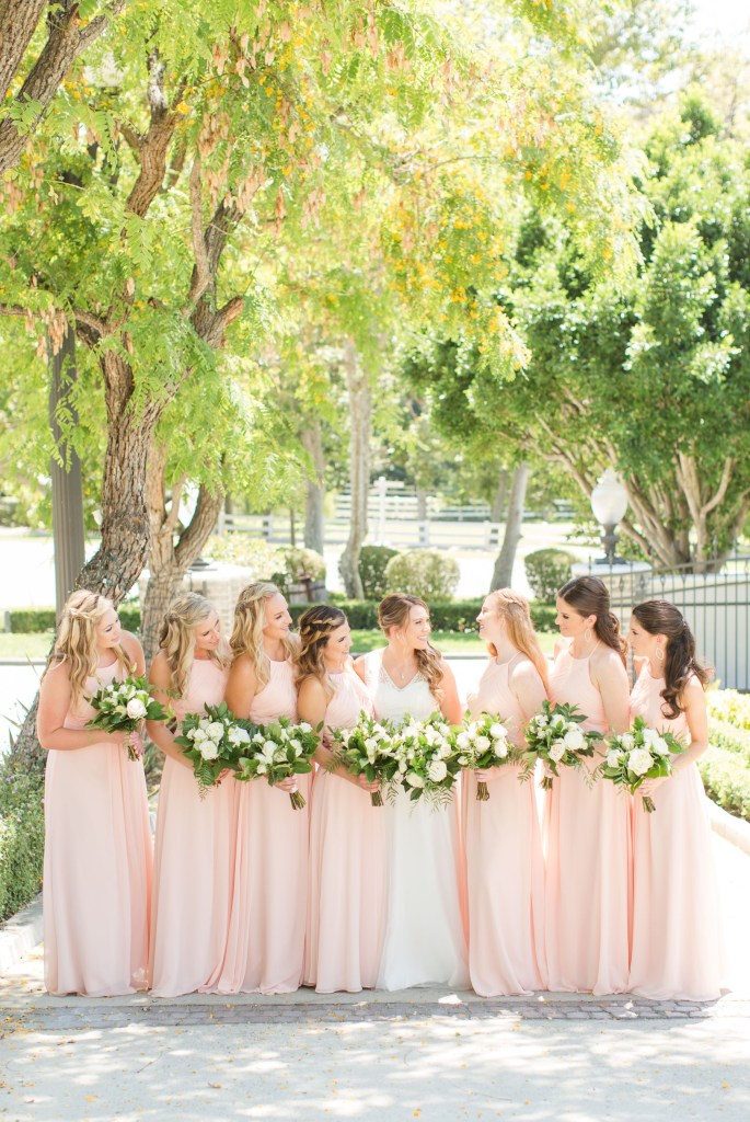 Bridesmaids in blush floor length azzize bridesmaid dresses holding white flowers with lots of grennery.