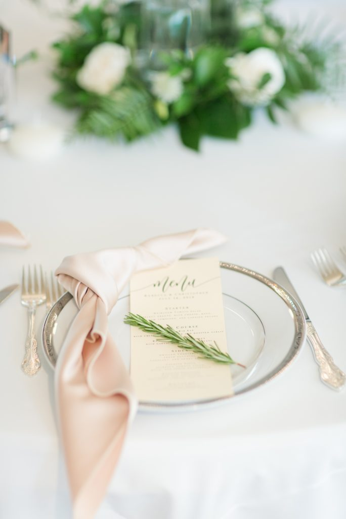 Serving plate  with a napkin and menu on it adored with a decorative sprig of rosemary.