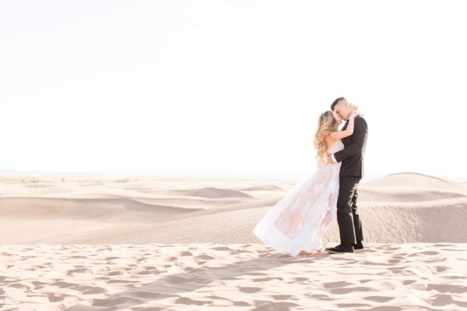 Couple kissing on top of a Sand Dune at the Great Sand Dunes National Park in Colorado. Colorado's best engagement session locations.