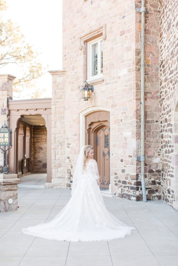Bride outside of highland ranch mansion in a lace dress.