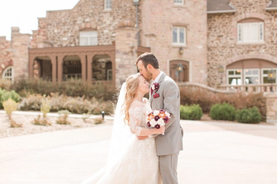 Bride and groom posing in front of the Highlands Ranch Mansion venue in Colorado.