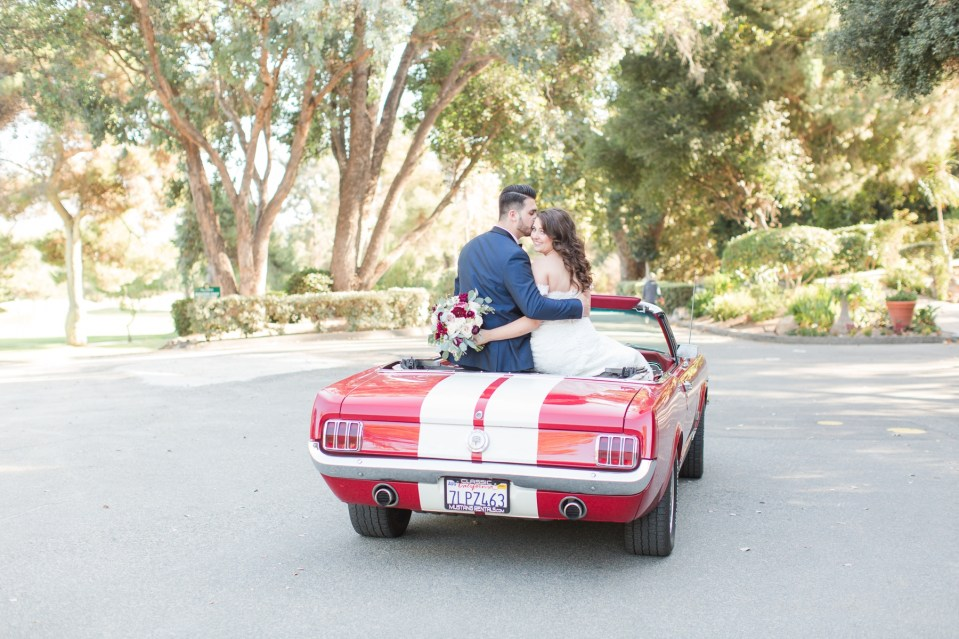 Bride and groom sitting in a red 1966 mustang