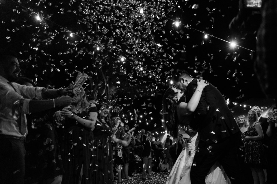 Bride and groom kissing during a confetti grand exit. Confetti falling over bride and groom. Unique wedding exit ideas.