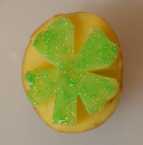 Children will love watching you make a sparkly green potato stamp for St. Patrick's Day!