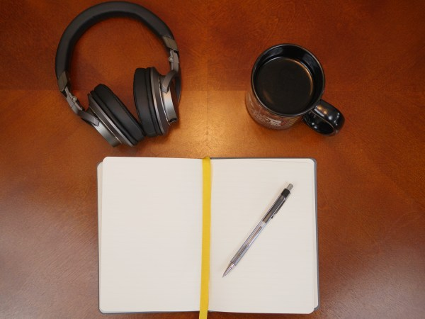 Flat lay photo of Audio Technica headphones with a notebook and black coffee. 3 Reasons Musical Gifts Make Dads Happy - Theresa's Reviews