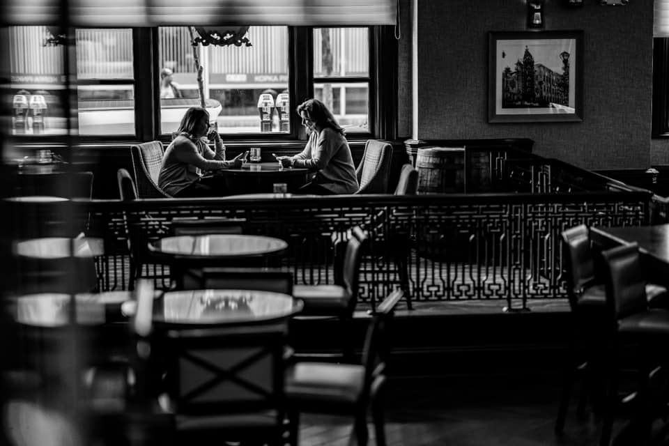 Two photographer friends take a social media break together at the hotel bar during the Reset Conference