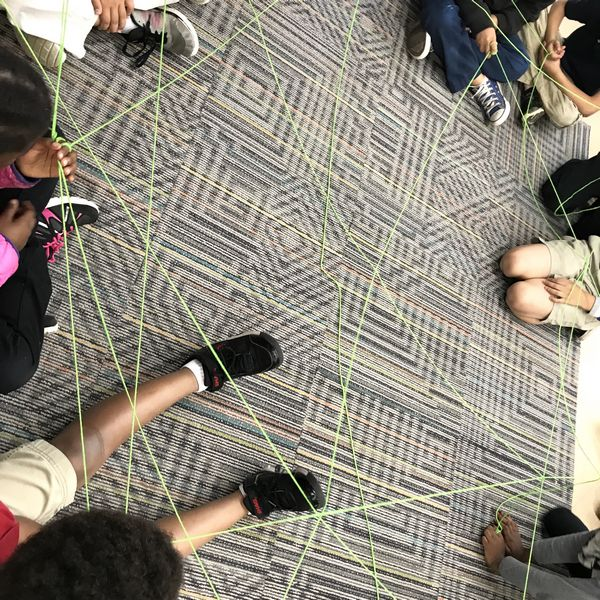 students on rug connected by string