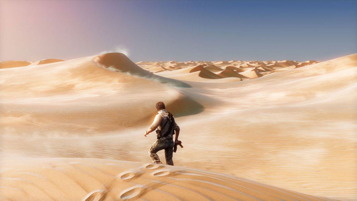 Nathan Drake walks away from the camera in a seemingly endless desert