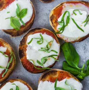 Homemade English muffins toasted with tomato sauce, fresh mozzarella, and fresh basil