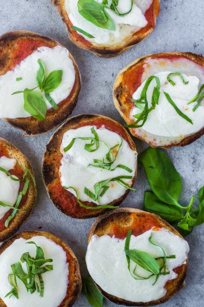 Homemade English muffins toasted with tomato sauce, fresh mozzarella, and fresh basil