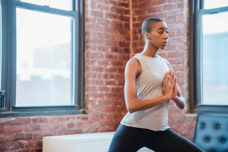black woman exercising anjaneyasana posture during yoga workout