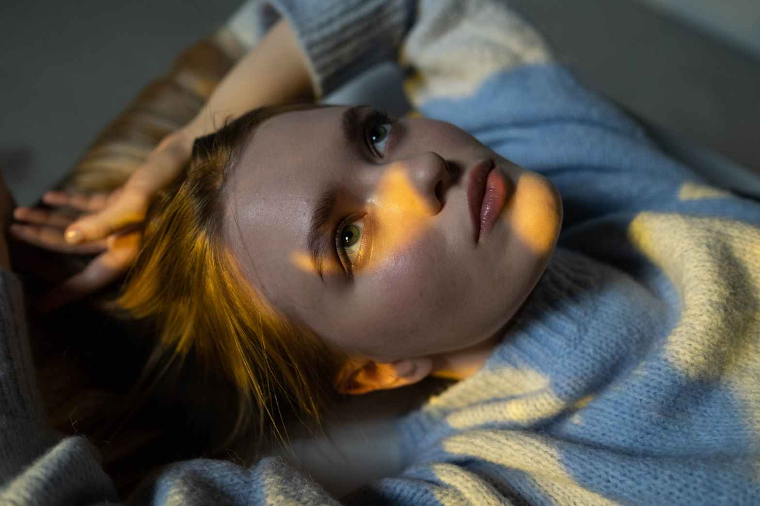 woman in blue sweater lying on bed