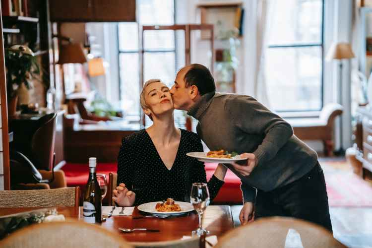 loving man kissing wife with dinner