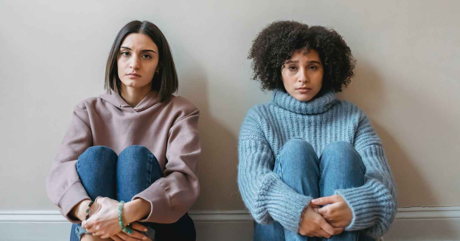 unhappy multiracial women sitting and hugging knees in light room