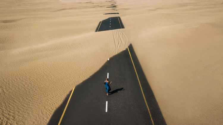 bird s eye view photography of road in the middle of desert