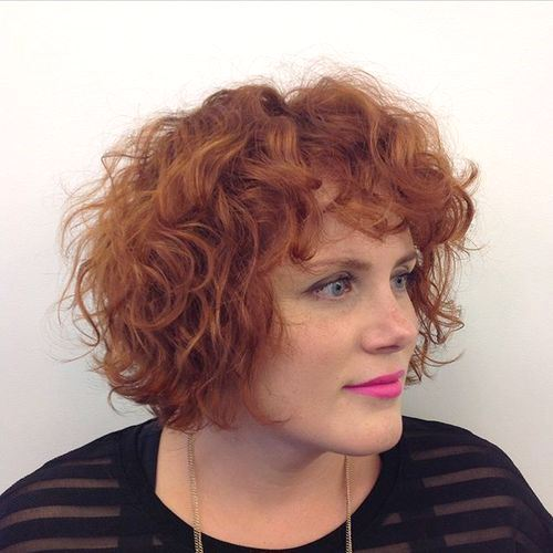 Short red curly hairstyle with bangs