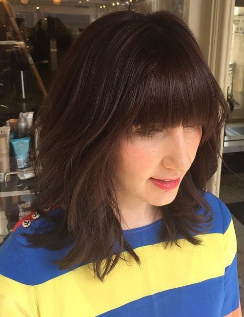 medium layered brown hairstyle with bangs