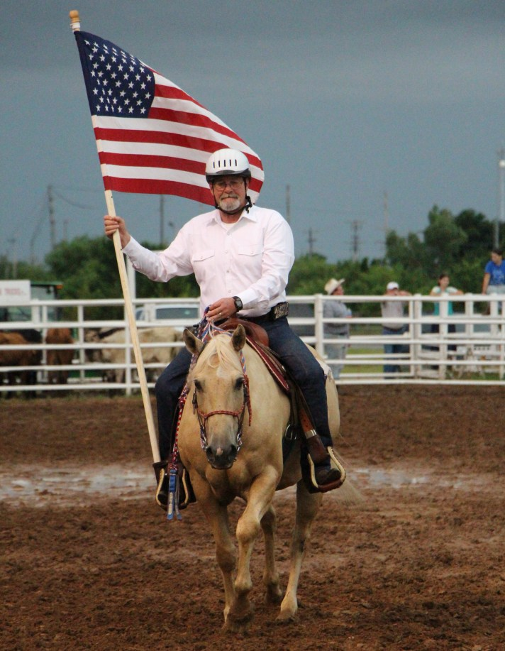 veteran holding a flag while riding a horse