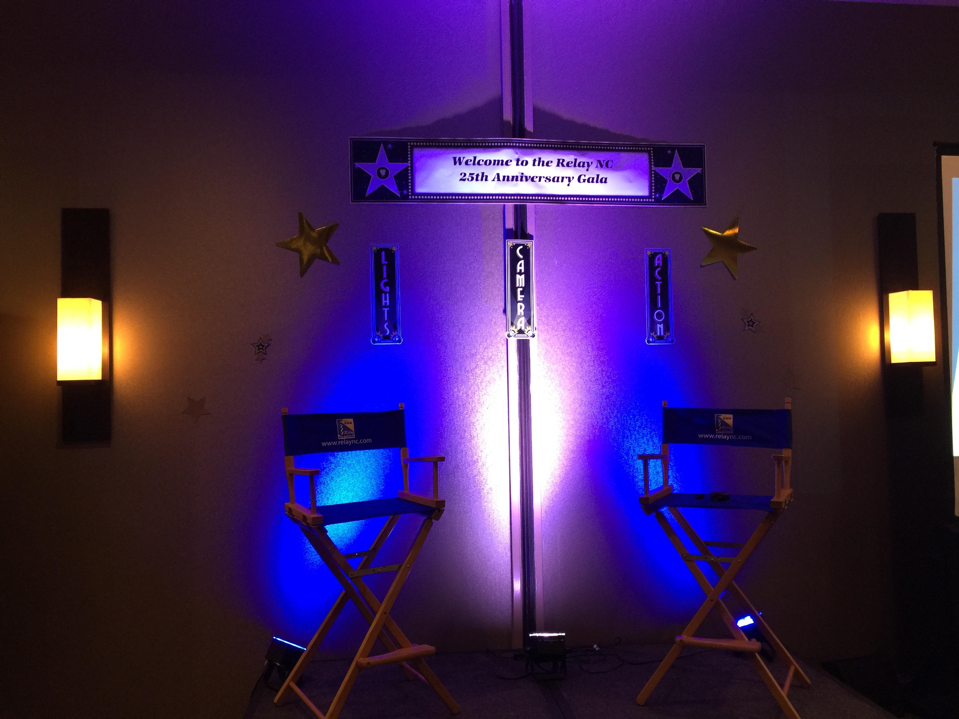 "In a dark room, on a stage, there are two director's chairs on either end with blue lights illustrating them. Above the platform is a sign that says ""Welcome to Relay NC 25th Anniversary Gala!"" with smaller signs below that proclaiming ""Lights!"", ""Cameras!"", and ""Actions."" There are also two golden stars on either side."
