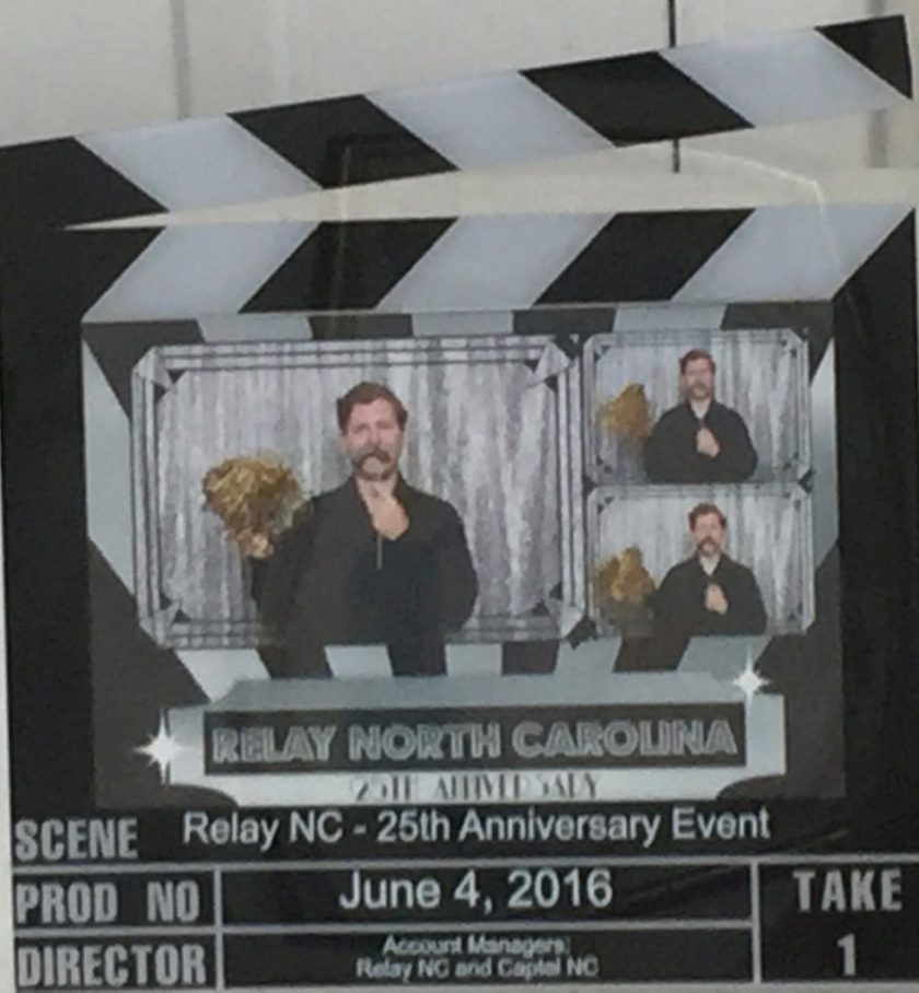 "Picture frame that looks like a movie take indicator with three images of a man (Patrick) with a silver mustache that he is holding on a stick in his left hand and in is right hand is a gold Pom Pom. He is wearing a black button down shirt and is standing in front of a silver background. The fame says on the bottom Scene: ""Relay NC 25th Anniversary Event"" PROD NO: ""June 4, 2016"" Director: ""Account Managers: Relay NC and Capital NC"" And on the bottom right of the frame says ""Take 1"""