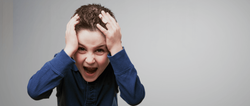 Boy with hands on head screaming