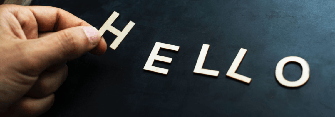 A hand placing the letters H E L L O on a blackboard