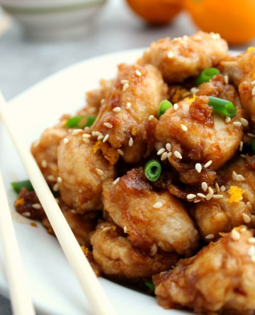 Copycat Panda Express Orange Chicken - served on a white plate with chop sticks