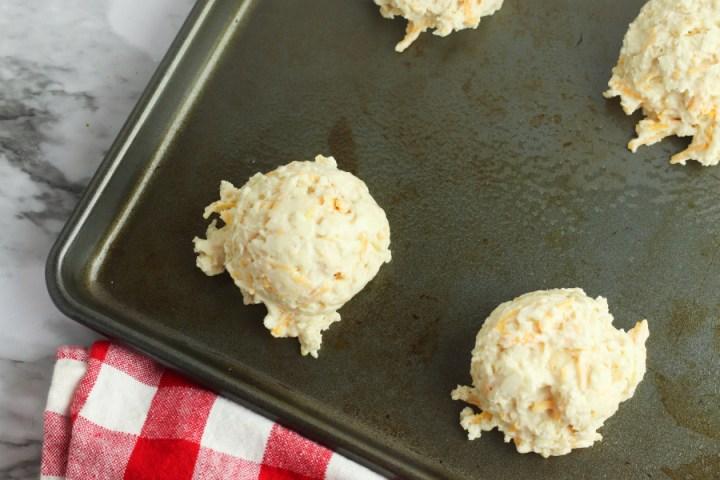 Cheddar biscuit batter balls on the baking sheet