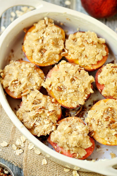 Halves of peaches sitting, topped with oat streusel topping, in a baking white baking dish