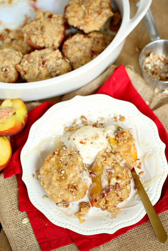 Streusel Topped Baked Peaches served on a white plate with a scoop of vanilla ice cream