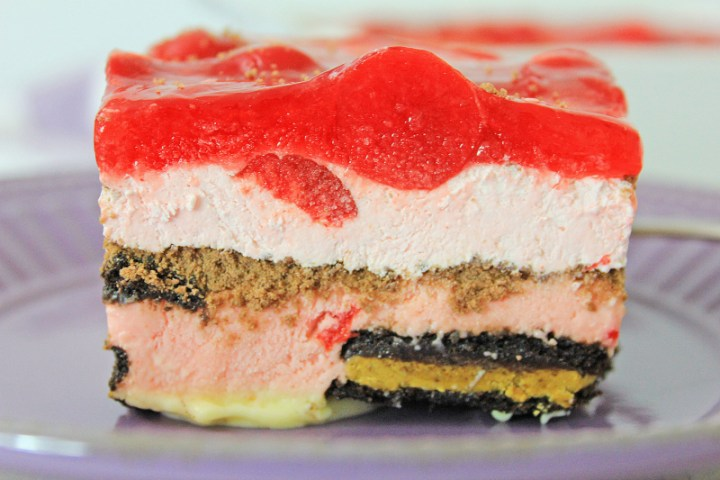 side view of a slice of Chocolate Cherry Oreo Icebox Cake on a purple plate