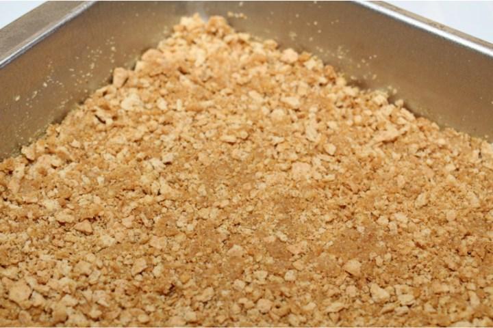 cracker crust being pressed into baking pan