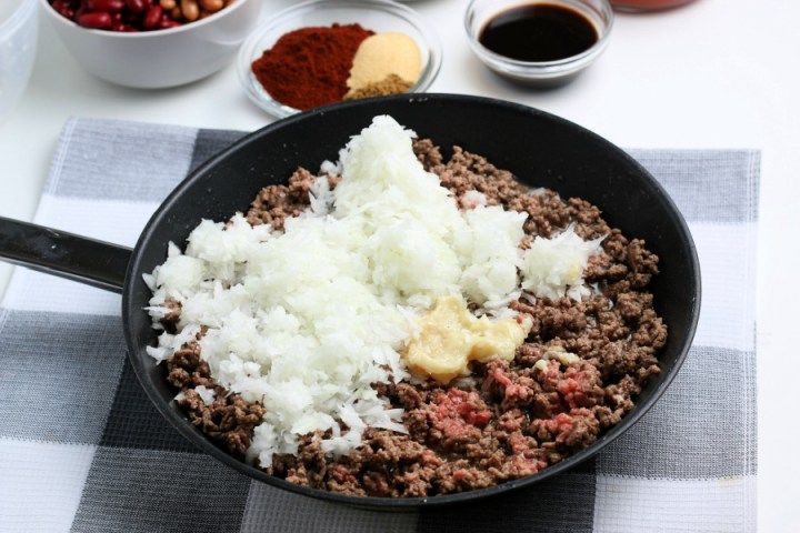 cooked ground beef, diced onion, and garlic in a frying pan