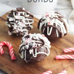 3 hot chocolate bombs on a cutting board with mini candy canes