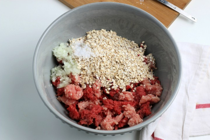 ingredients for meatballs in a mixing bowl