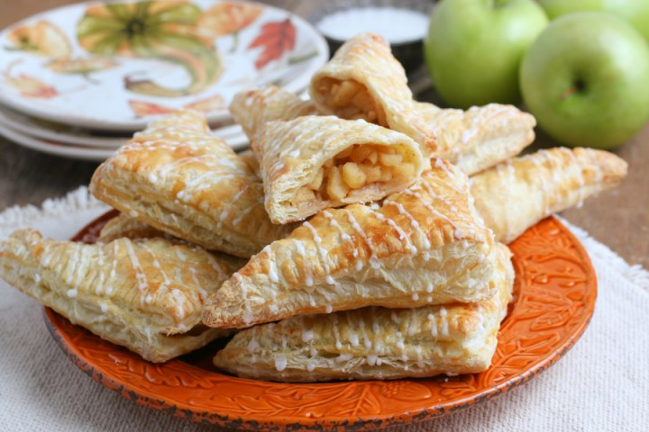 apple turnovers stacked on an orange plate