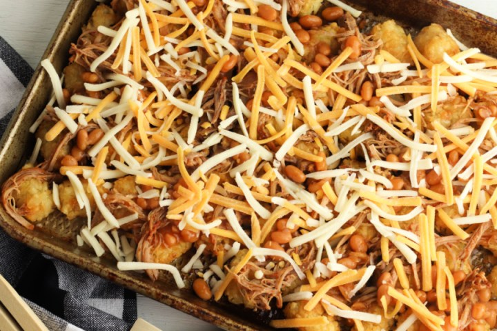 tater tots topped with bbq pork, beans and shredded cheese on a baking sheet