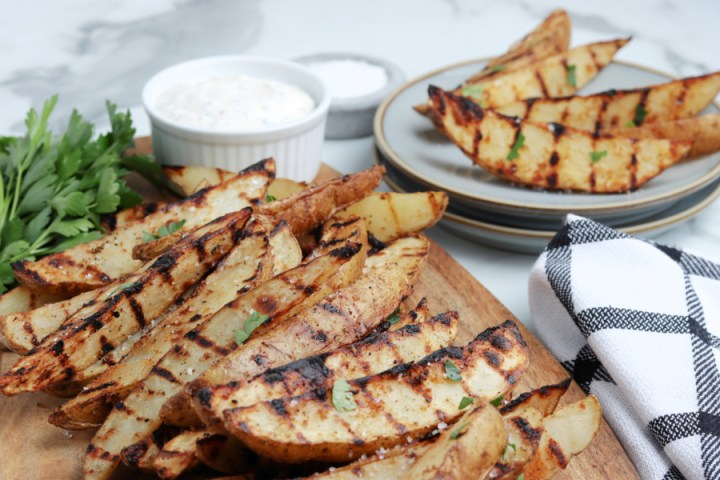 grilled potato wedges on cutting board
