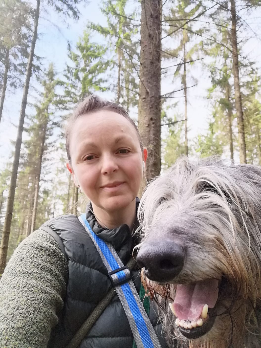 A photo of a woman smiling walking in the woods with her dog on a bright spring day